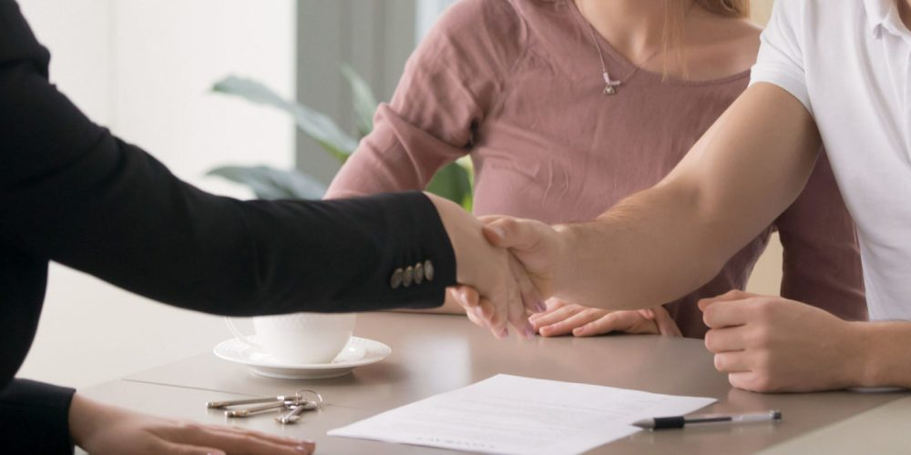 Horizontal concept photo married couple meeting at office with realtor agent shaking hands after signing real estate contract. Buy purchase property, rent house flat, banner for website header design